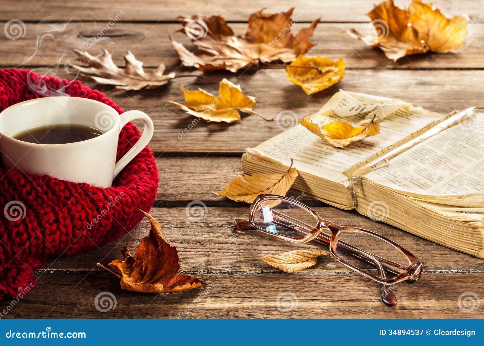 Café, livro, vidros e folhas de outono quentes no fundo de madeira