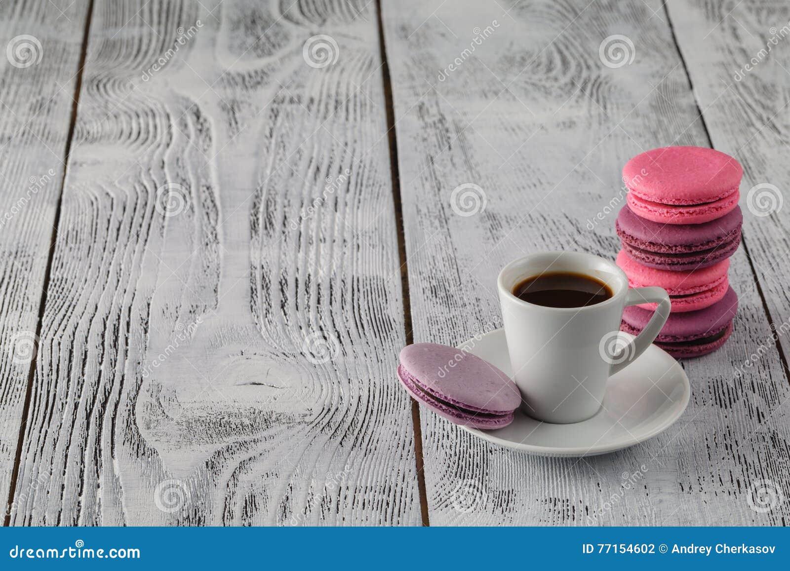 Café, macarons et crème sur une table blanche