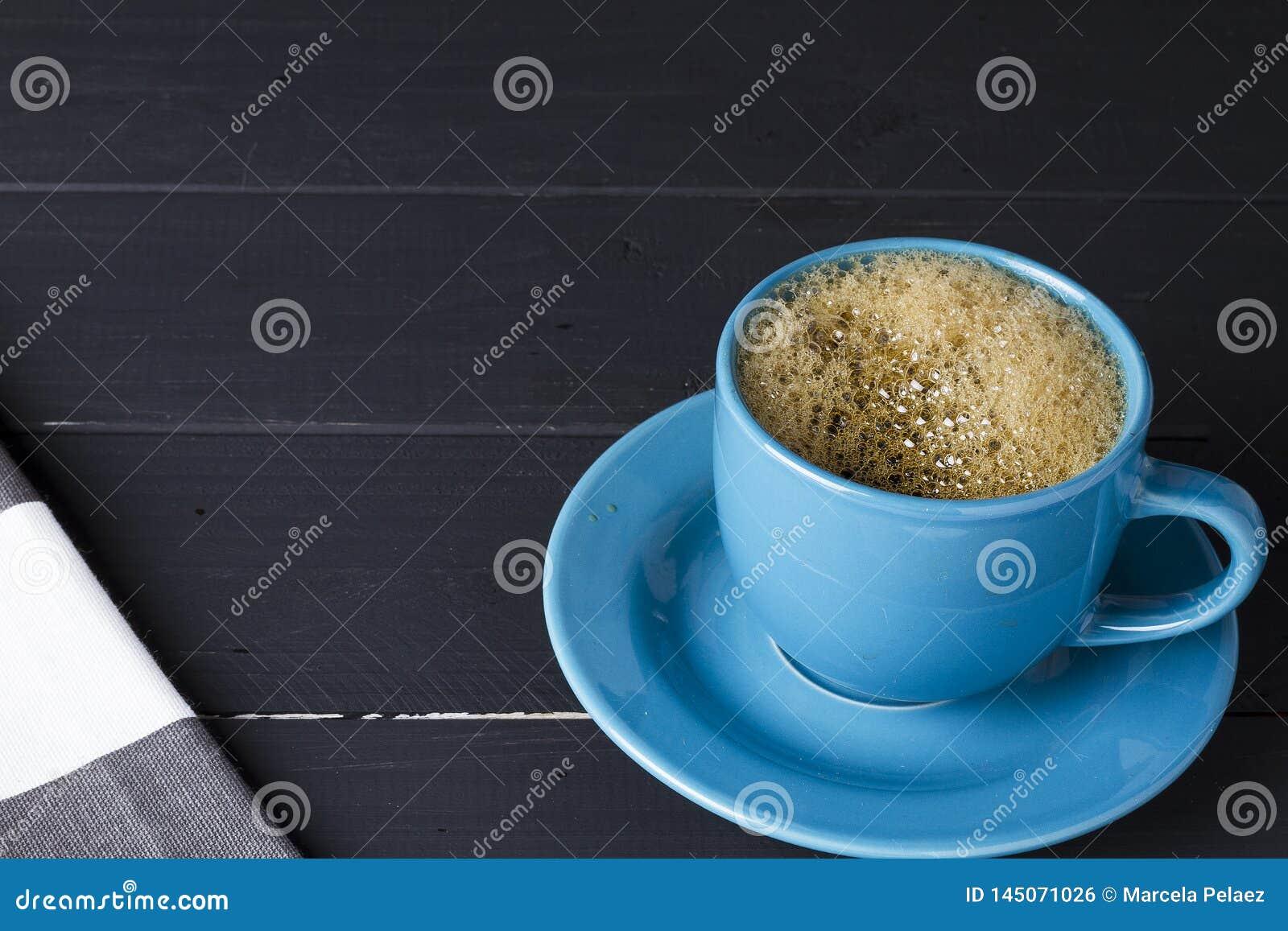 Café no copo azul com o prato de harmonização no fundo de madeira preto