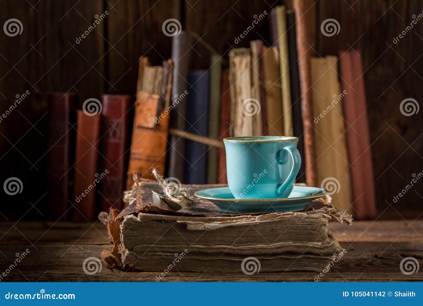Café no livro na porcelana azul na biblioteca