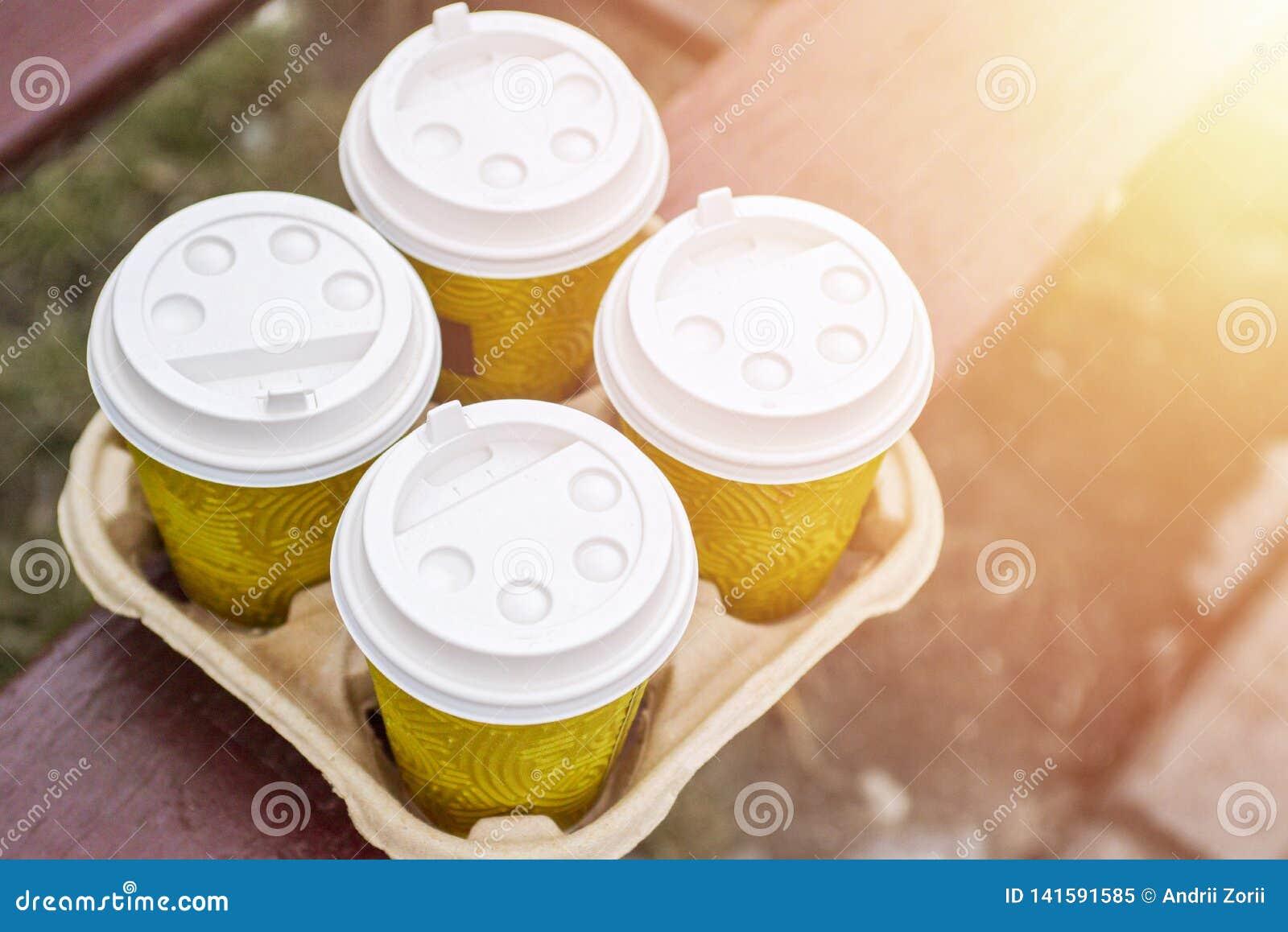 Café para llevar cuatro en sostenedor Tome el café para trabajar para la oficina entera Concepto del tiempo del café