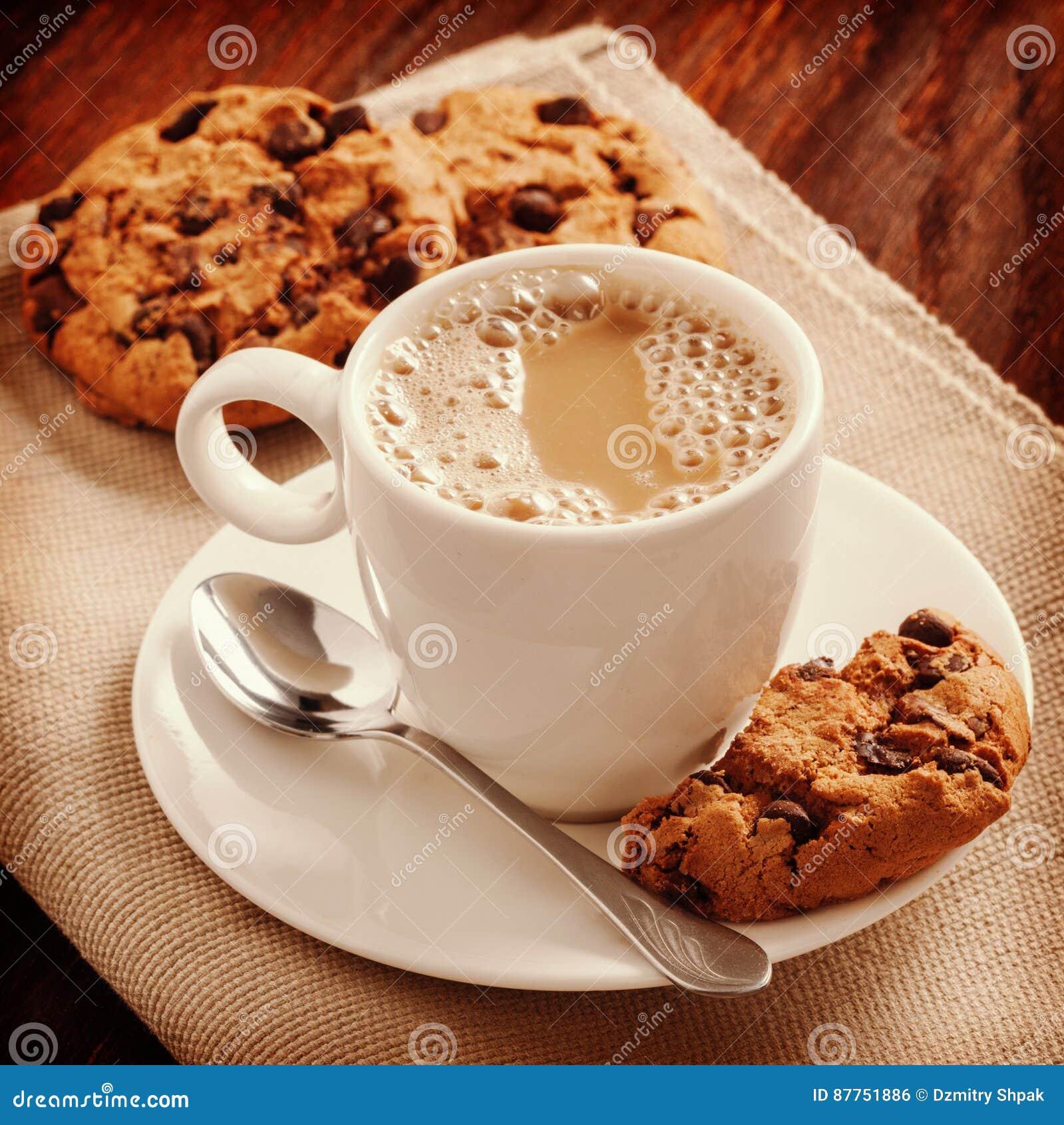 Café parfumé en chemise blanche et biscuits sur la table