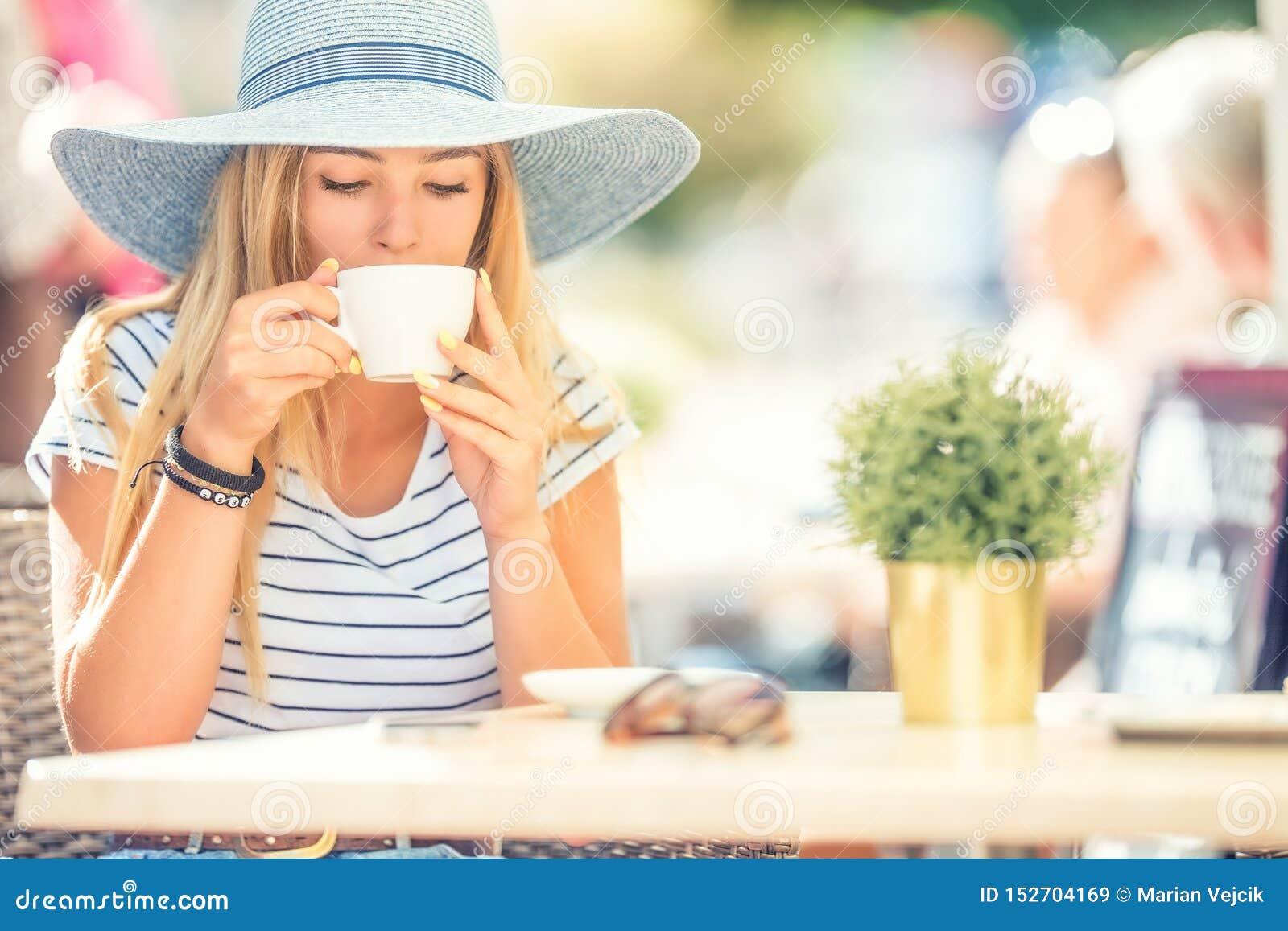 Café potable de belle fille dans une terrasse de café Jeune femme de portrait d été