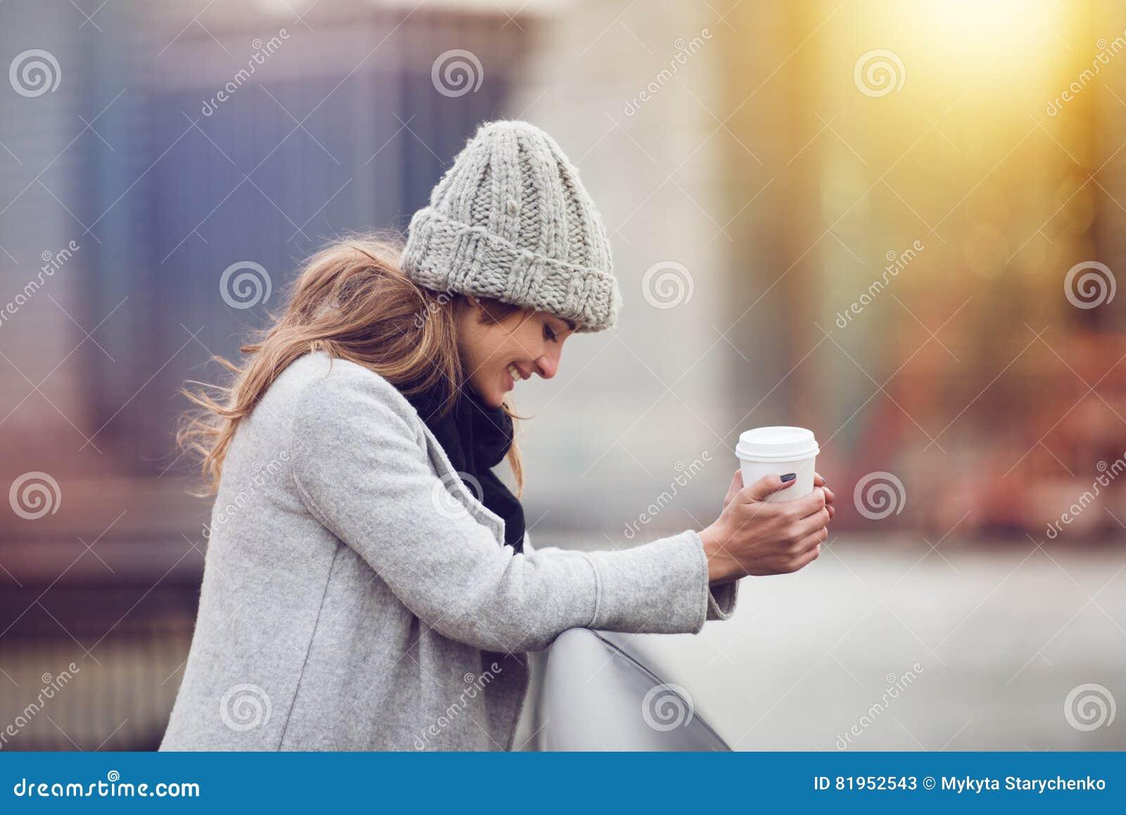 Café potable de belle jeune femme adulte heureuse près des vêtements de port et du sourire d hiver d horizon de New York City