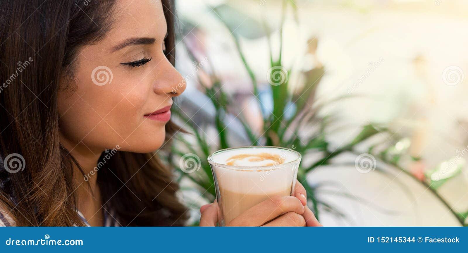 Café potable de femme en café, appréciant son matin