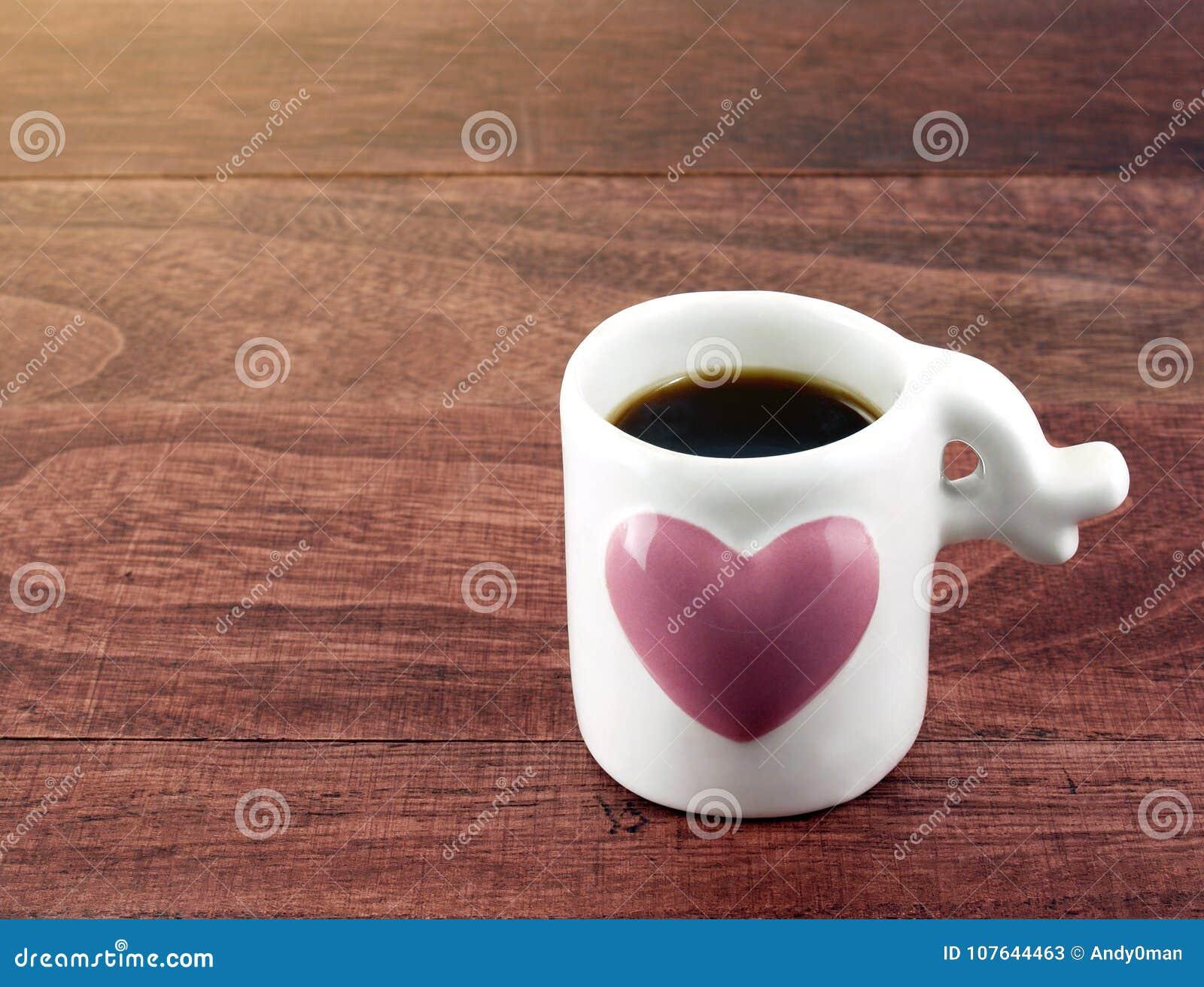 Café preto do close-up no copo de café branco pequeno com coração cor-de-rosa grande no assoalho de madeira da tabela do marrom e