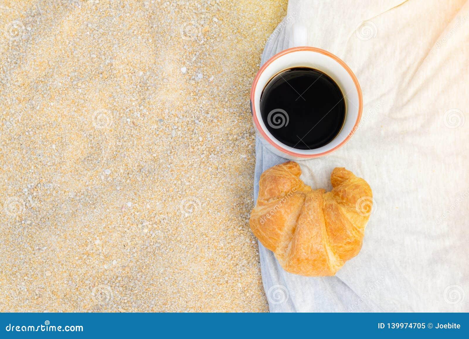 Café preto e croissant no fundo da areia, no café da manhã na praia, no alimento e no conceito da bebida
