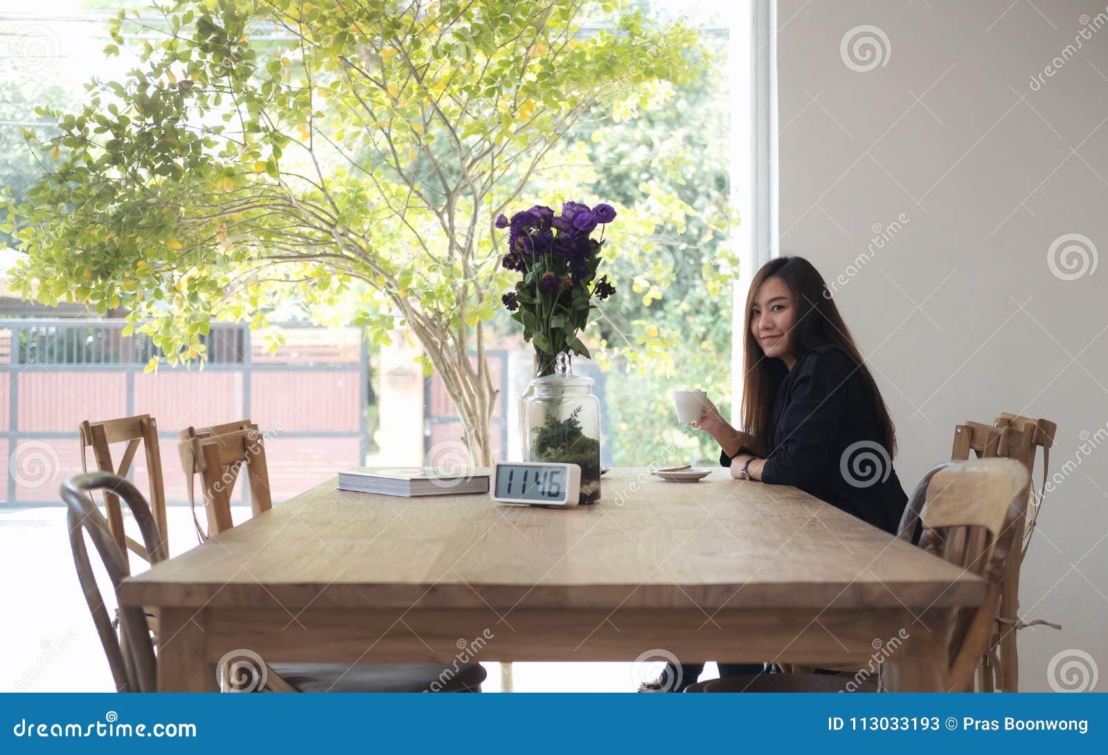 Café que se sostiene y de consumición de la mujer asiática hermosa con la sensación relajado en café