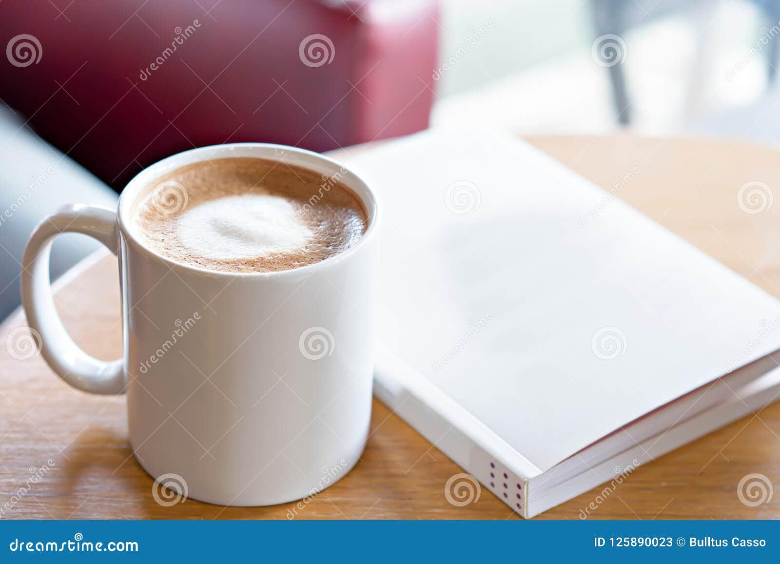 Café quente com o livro na tabela Tome um conceito da ruptura