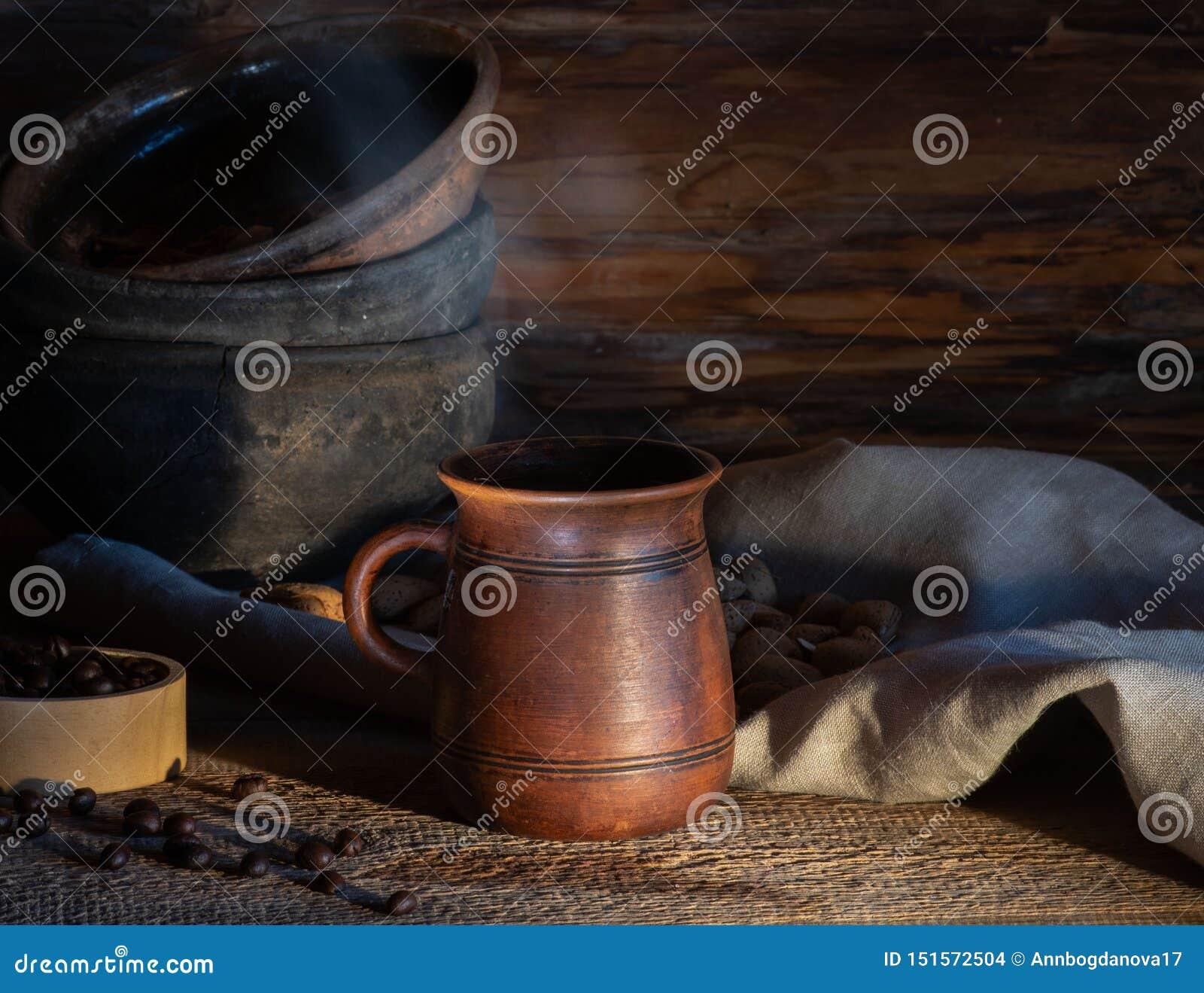 Café quente em uma caneca com vapor em uma placa de madeira na perspectiva dos utensílios de mesa cerâmicos velhos Estilo r?stico
