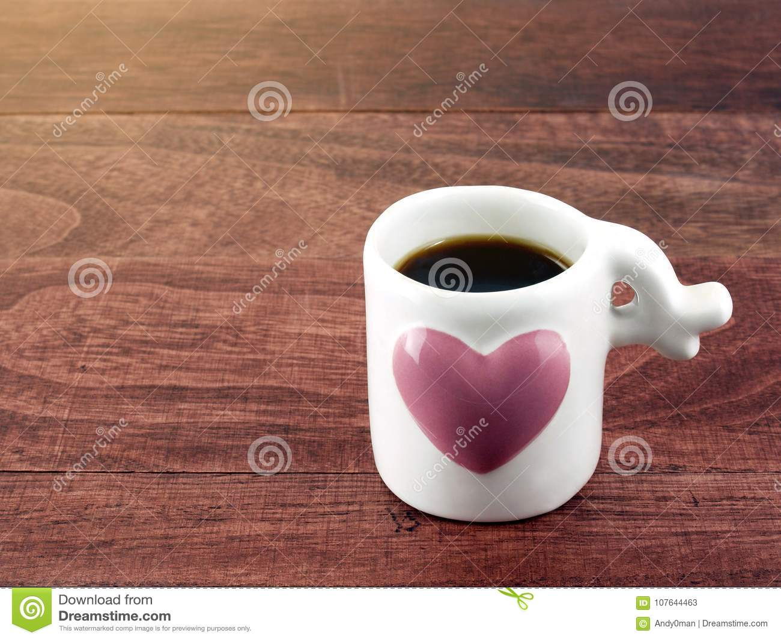 Café sólo del primer en pequeña taza del café con leche con el corazón rosado grande en piso de madera de la tabla del marrón osc