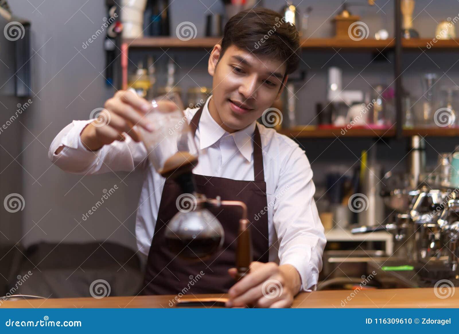 Café se renversant de jeune barman caucasien beau asiatique avec Sipho