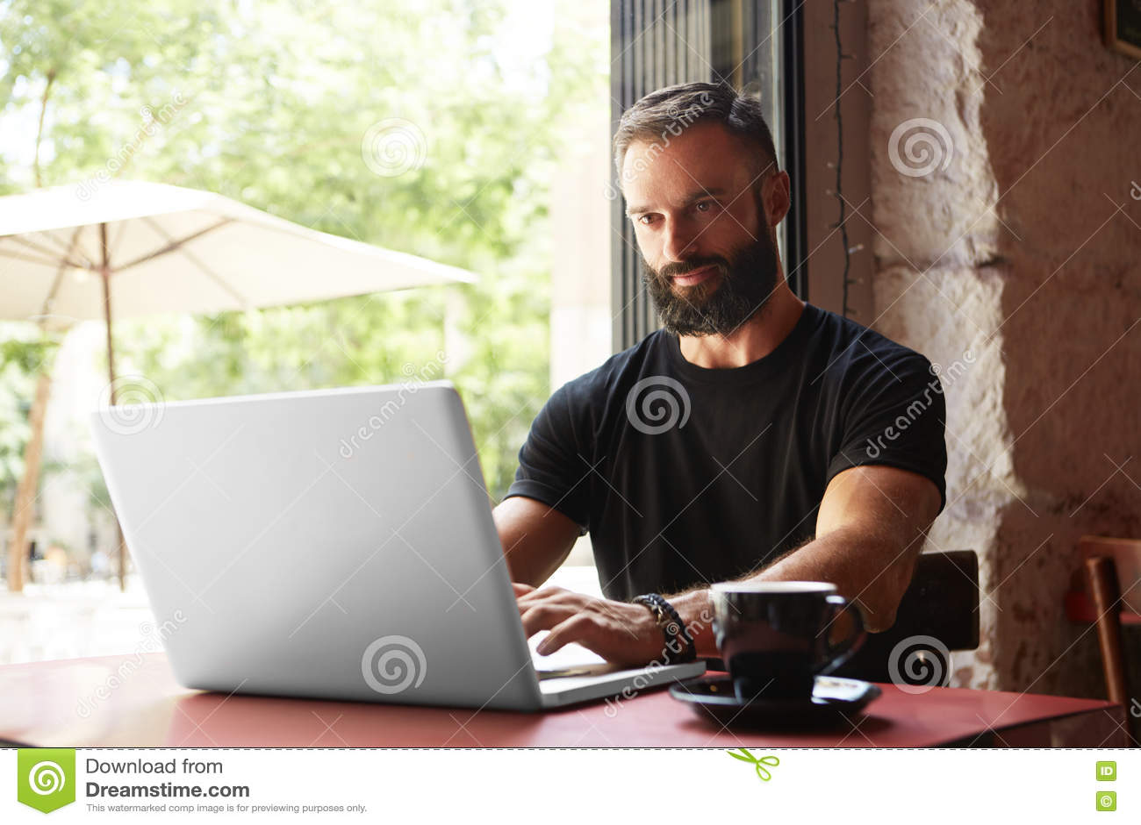 Café urbano de trabalho da tabela de madeira do portátil de Wearing Black Tshirt do homem de negócios farpado considerável Gerent