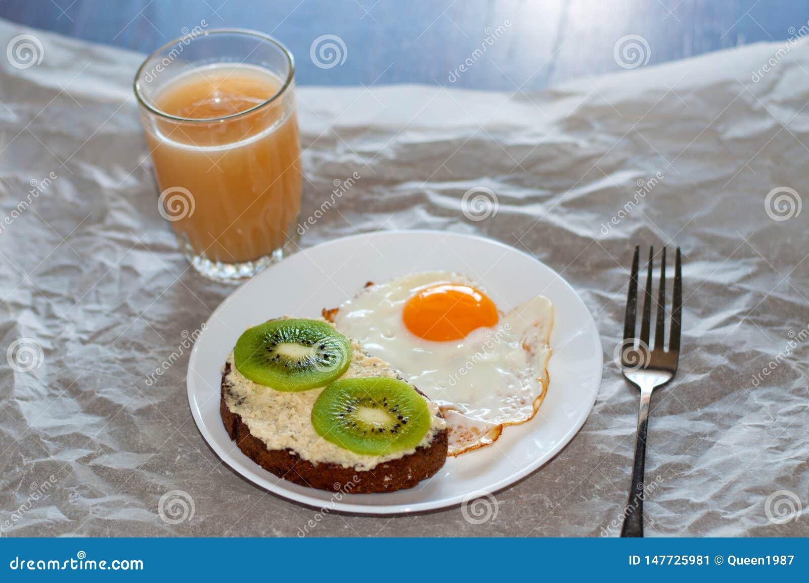 Caf? da manh? saud?vel e saboroso, suco, sandu?che wholegrain com quivi e ovo frito na placa branca