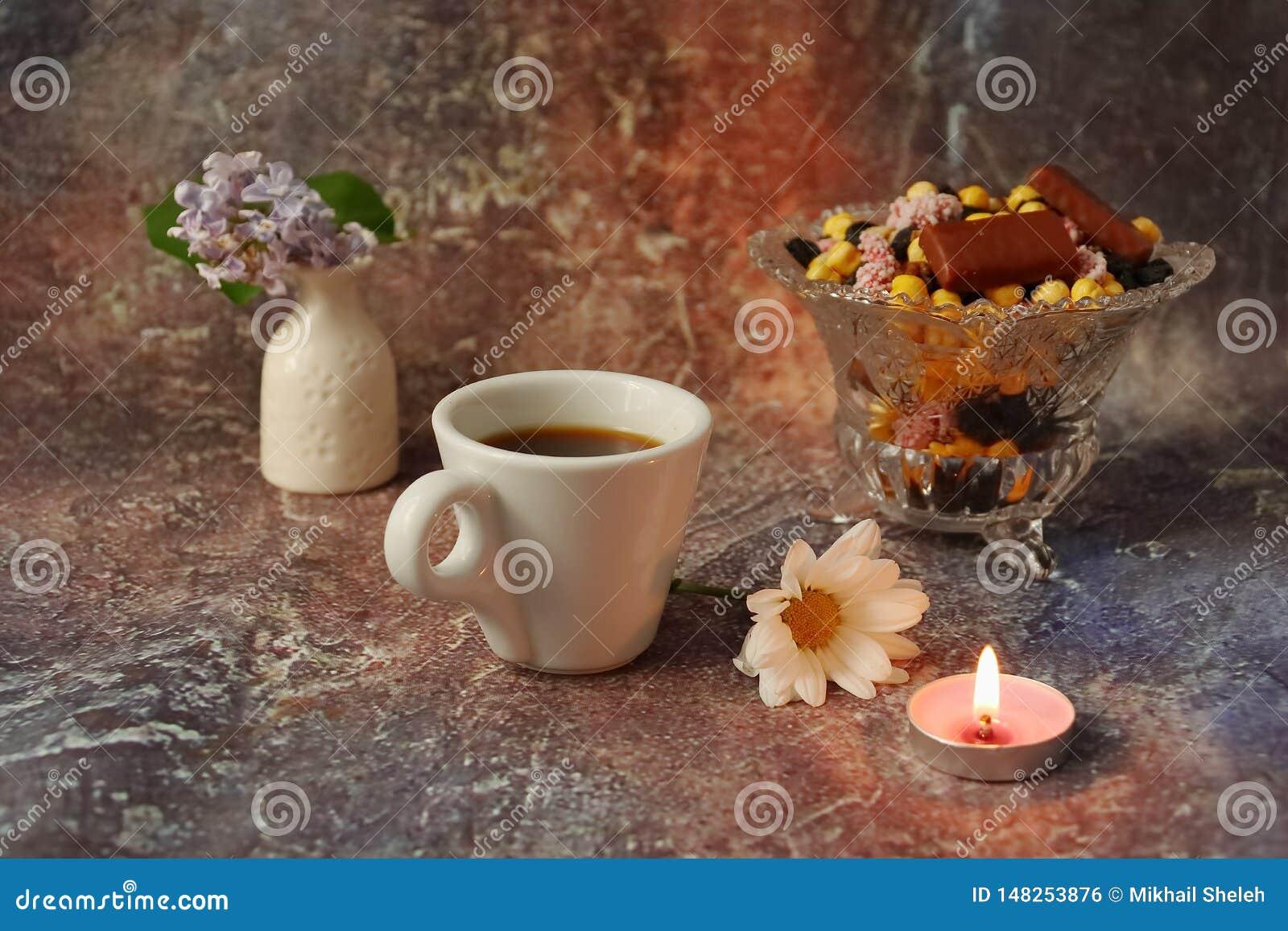 Caf? de la ma?ana a toda prisa: una taza de caf?, de flores en un florero, de frutas secadas y de dulces en un florero, una vela