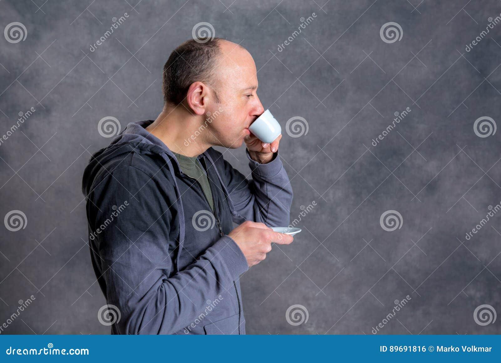 Caffè bevente del giovane uomo calvo