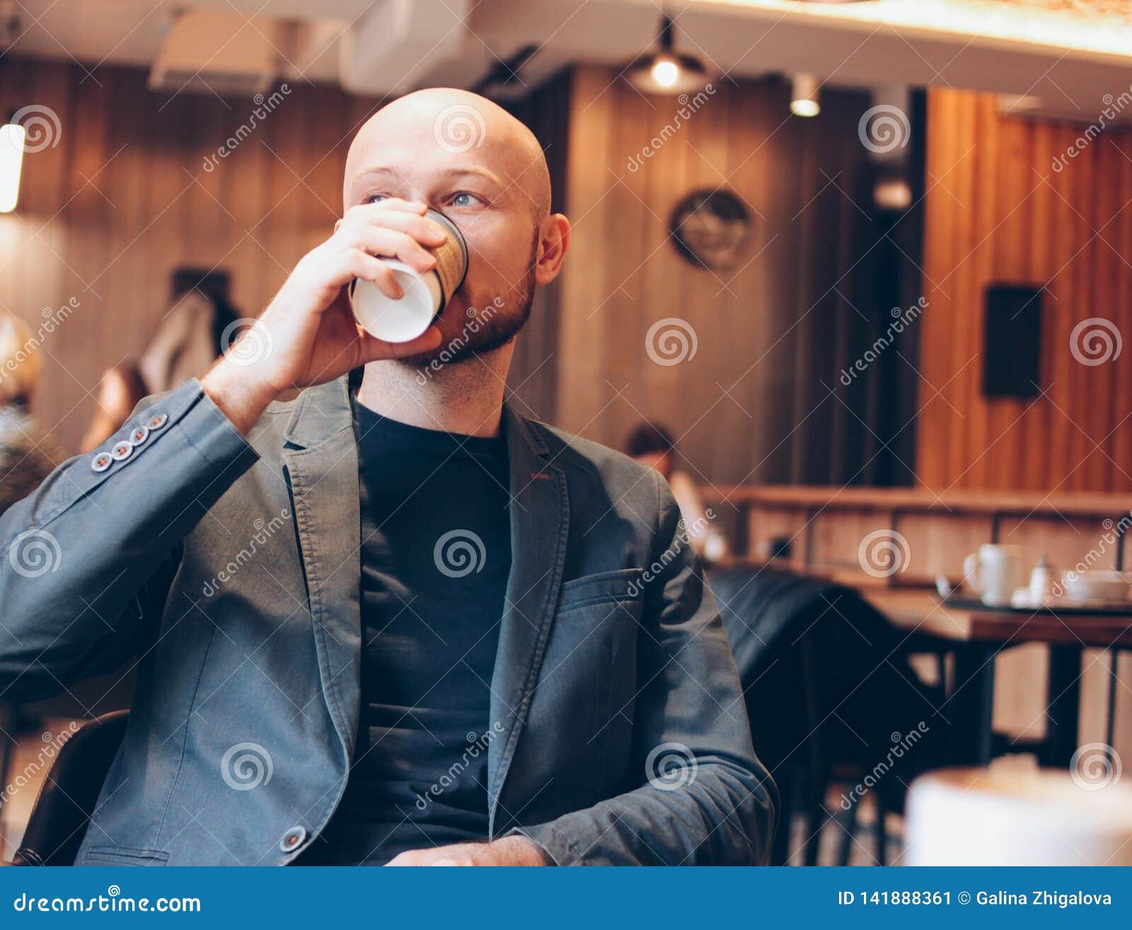 Caffè bevente dell uomo calvo adulto dalla tazza di carta ed esaminare nella finestra il caffè