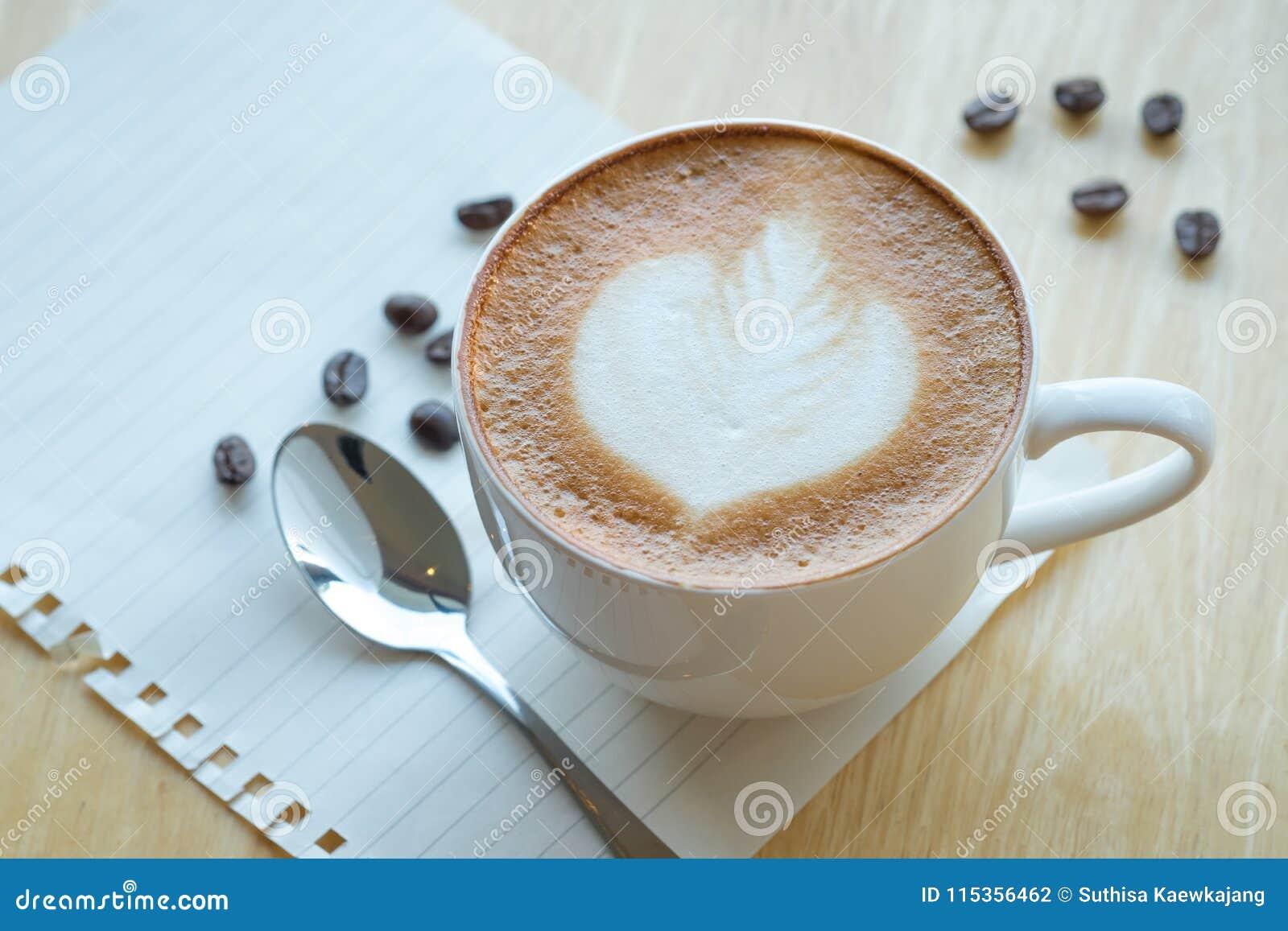 Caffè di arte del Latte e chicchi di caffè arrostiti sul backg di legno della tavola