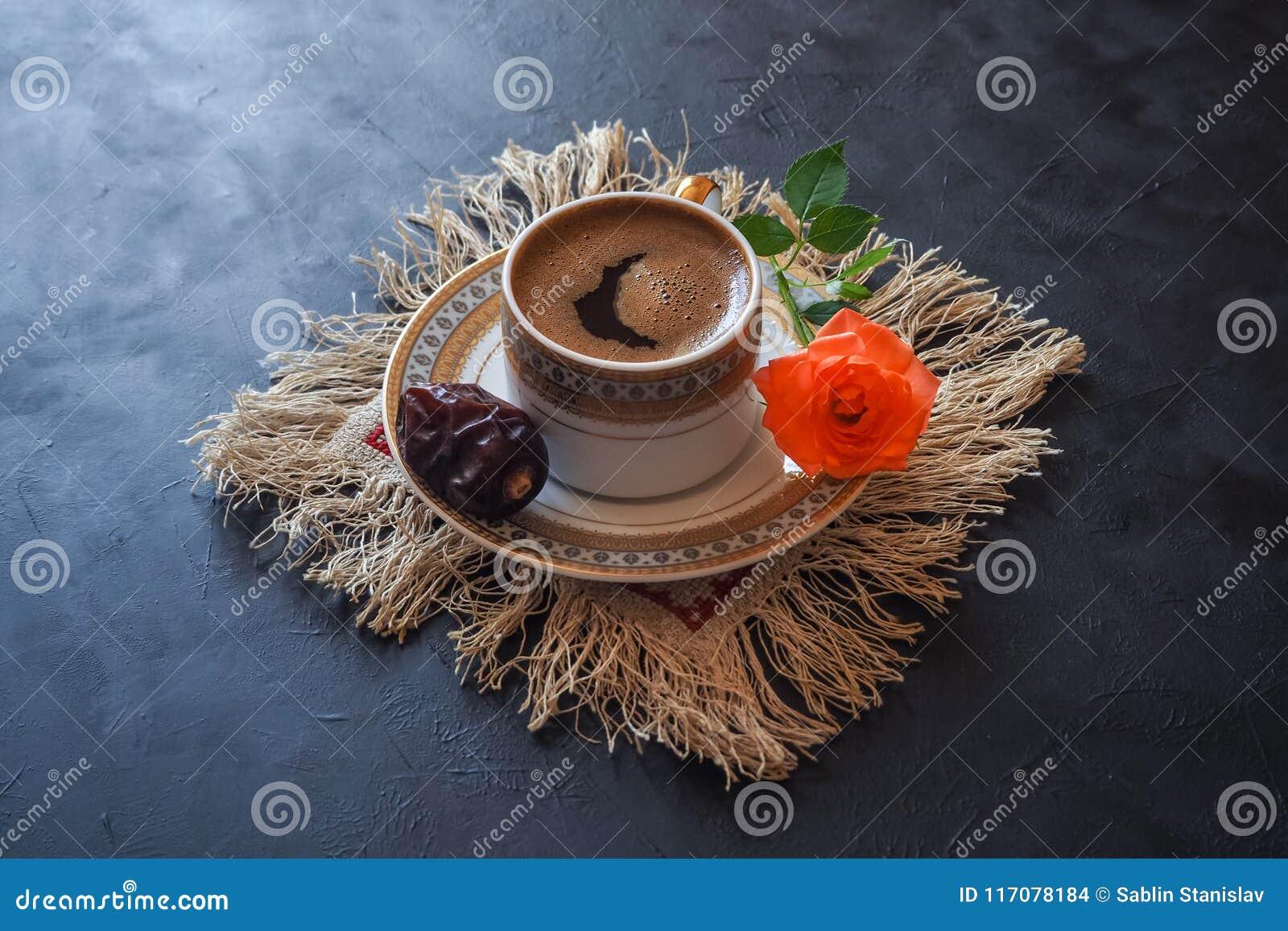 Caffè nero e datteri sulla tavola nera Alimento dolce per il Ramadan