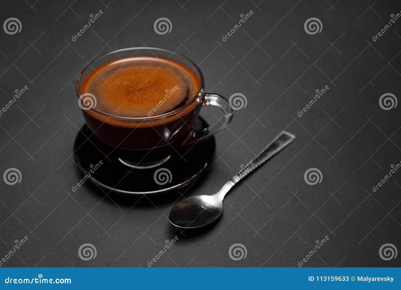 Caffè nero, naturale, fragrante nella tazza trasparente su un fondo nero