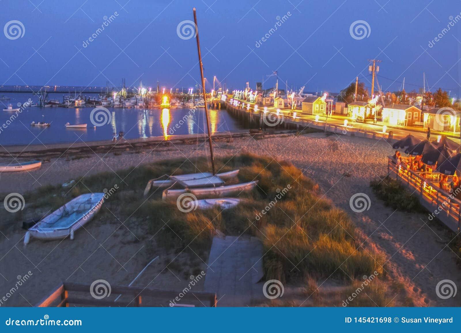 Cais de MacMillan na ponta de Cape Cod EUA na noite - um cubo ocupado para a pesca e as balsas - com os turistas na plataforma de