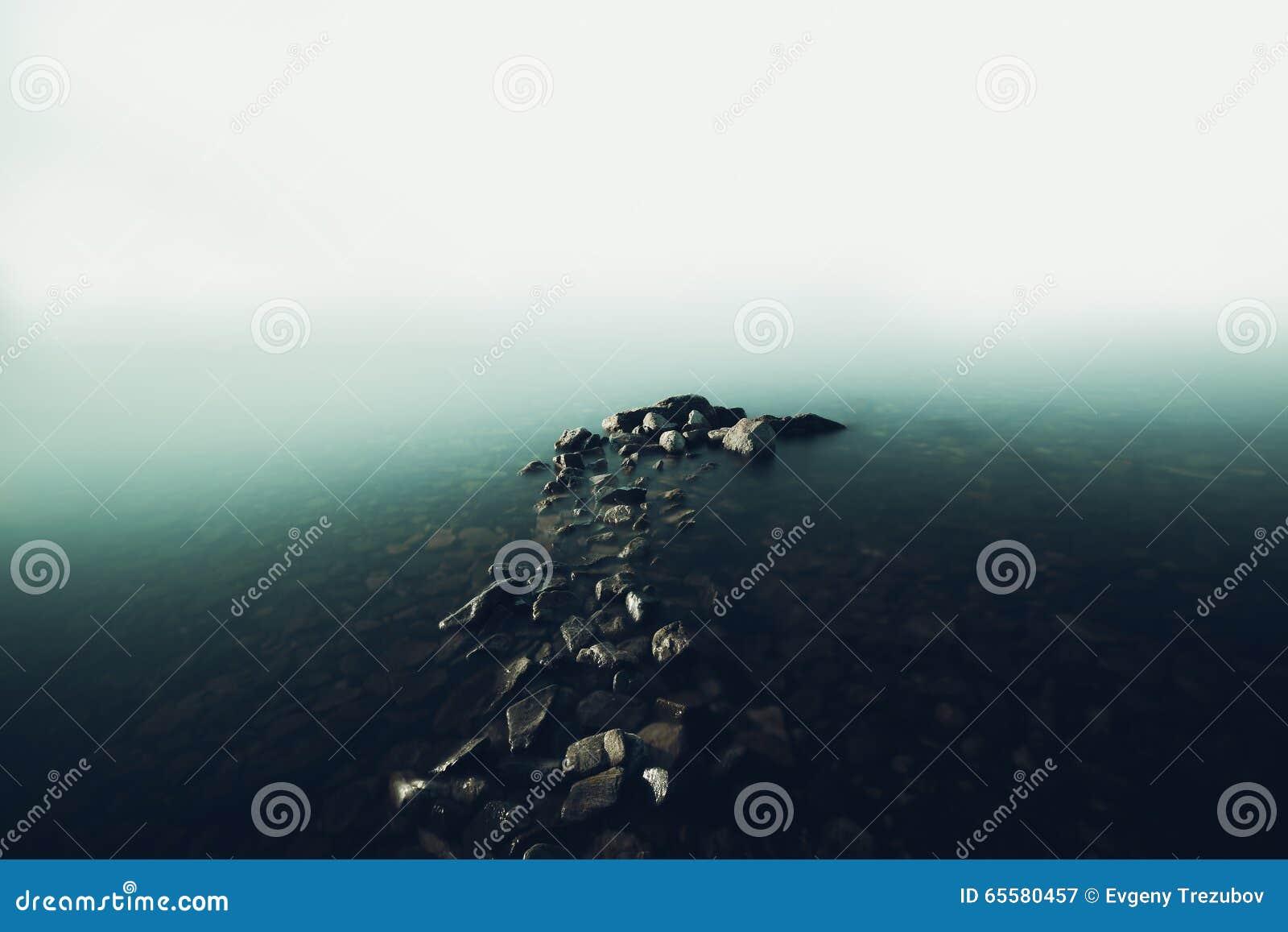 Cais de pedra na névoa no Lago Baikal
