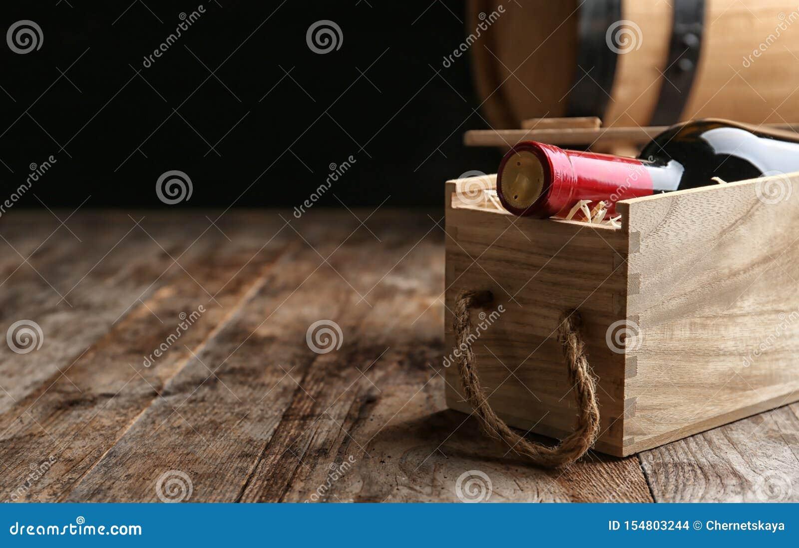 Caixa com a garrafa do vinho na tabela de madeira Espa?o para