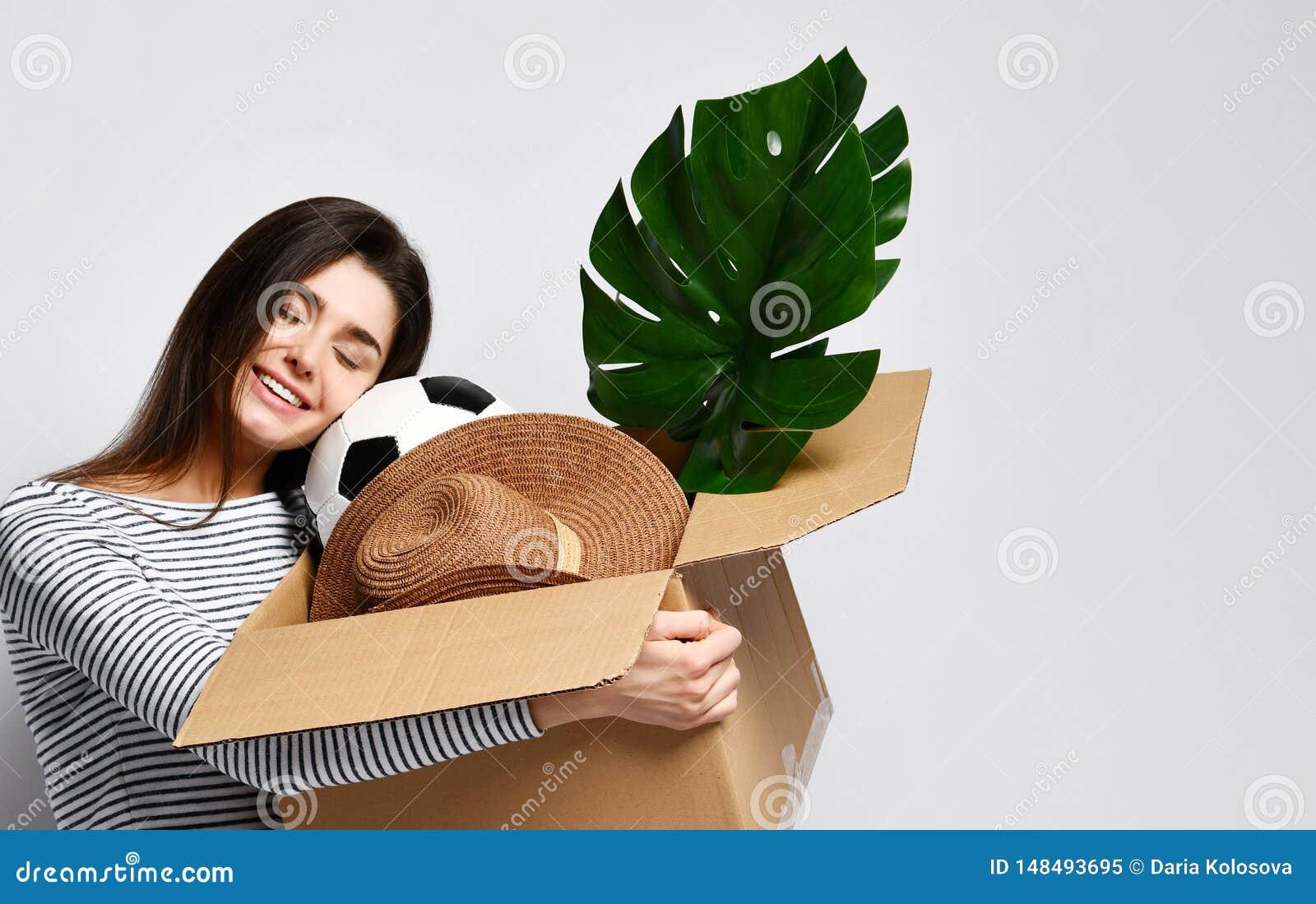 Caixa da terra arrendada da jovem mulher com coisas