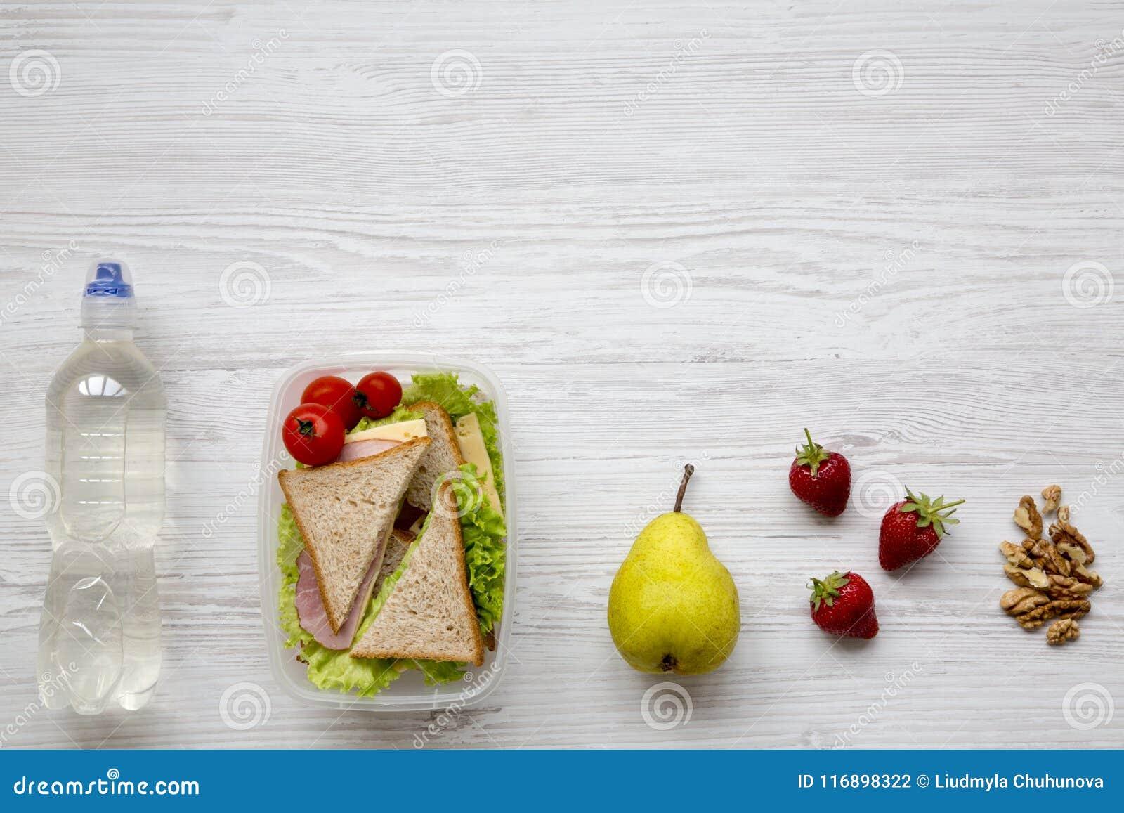 Caixa de almoço escolar saudável com os sanduíches, as nozes, frutos e a garrafa orgânicos frescos dos vegetais da água no fundo