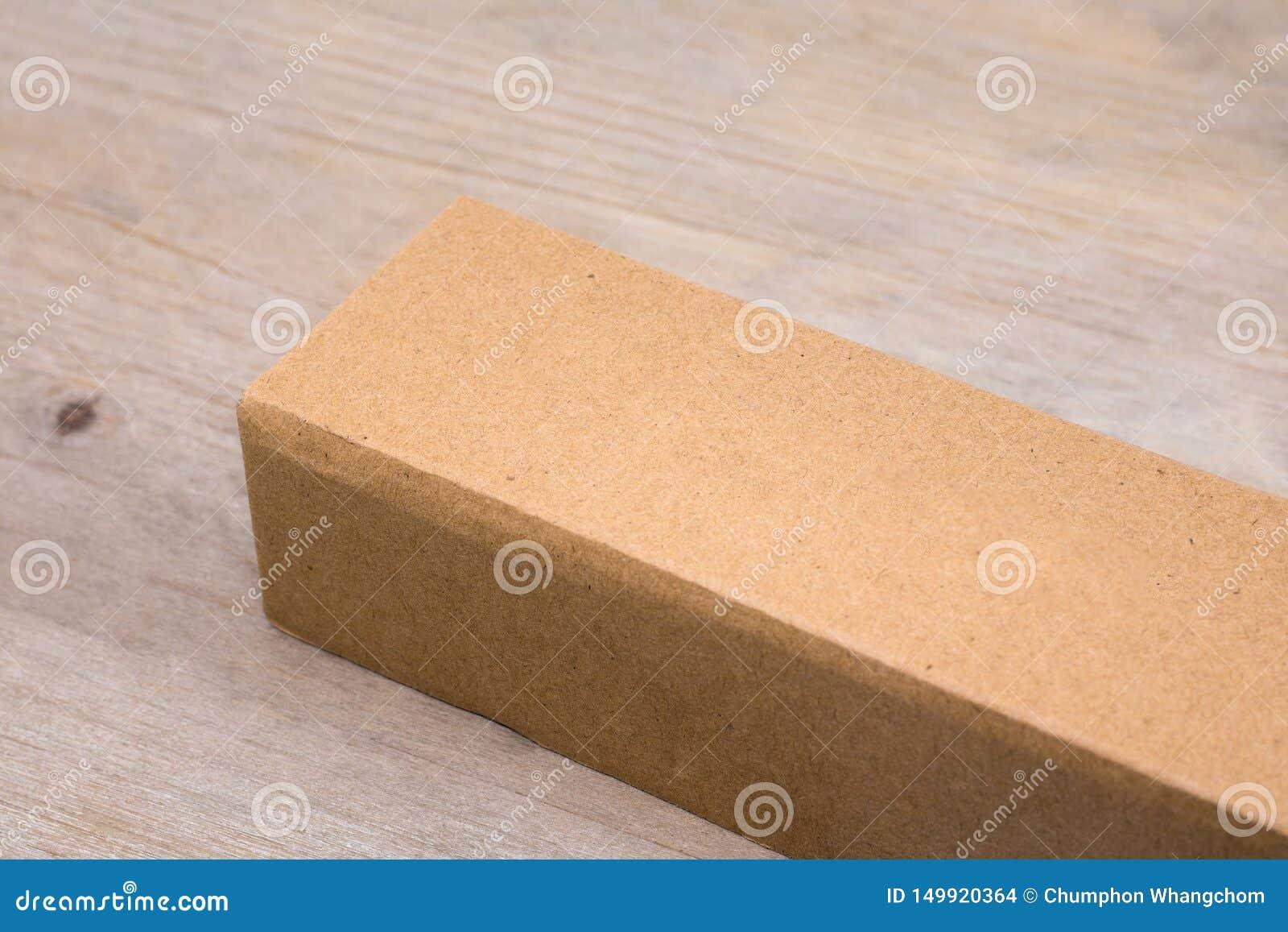 Caixa de cartão no fundo de madeira da tabela Molde da caixa longa para seu projeto Empacotamento reciclado do produto