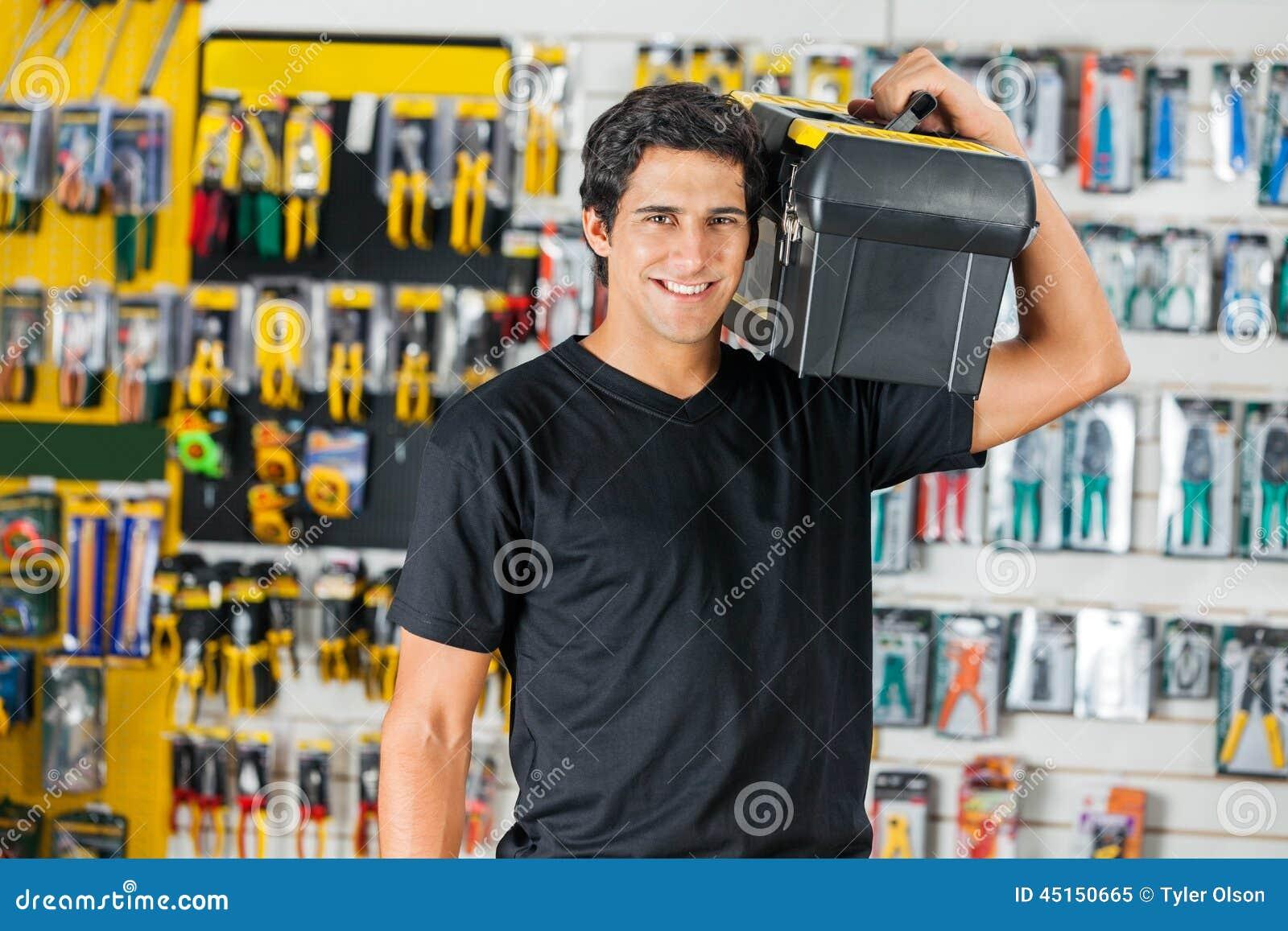 8a6727418 Retrato da caixa de ferramentas levando de sorriso do homem novo no ombro na  loja de ferragens