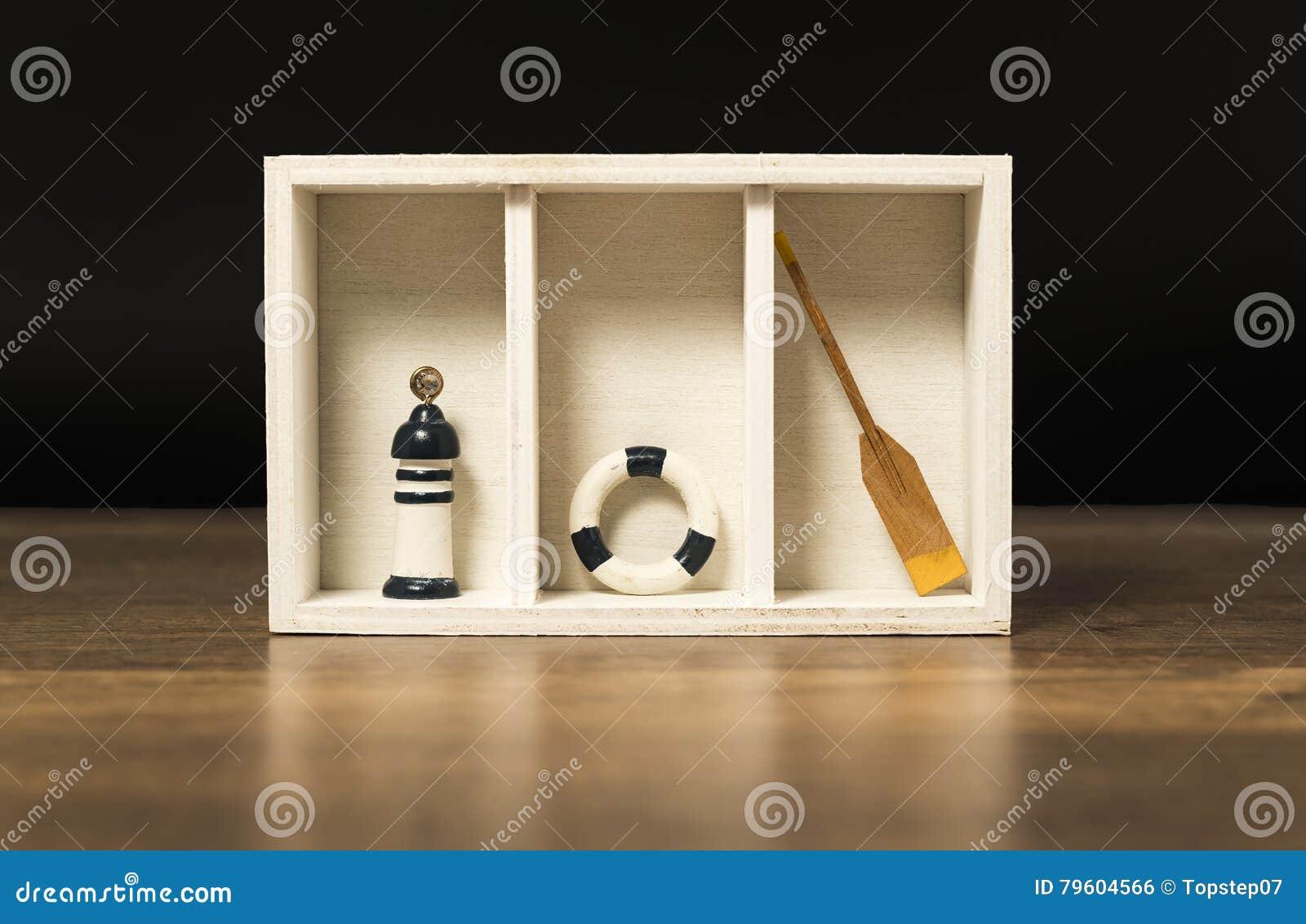Caixa de madeira branca com boia salva-vidas, pá e farol