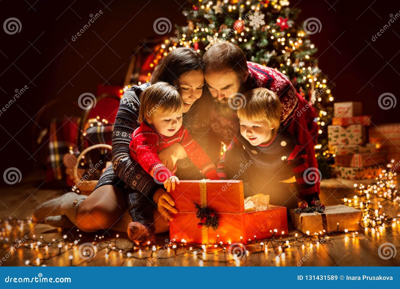 Caixa de presente atual leve aberta da família do Natal sob a árvore do Xmas, pai feliz Children da mãe