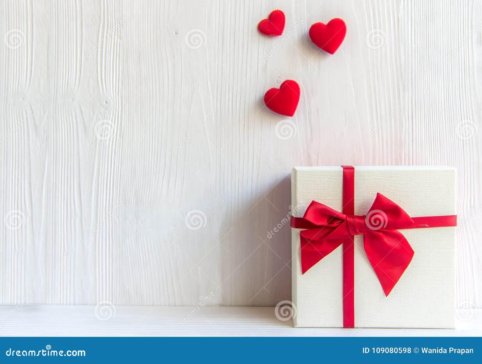 Caixa de presente branca do dia de Valentim com uma curva vermelha no fundo branco da parede,