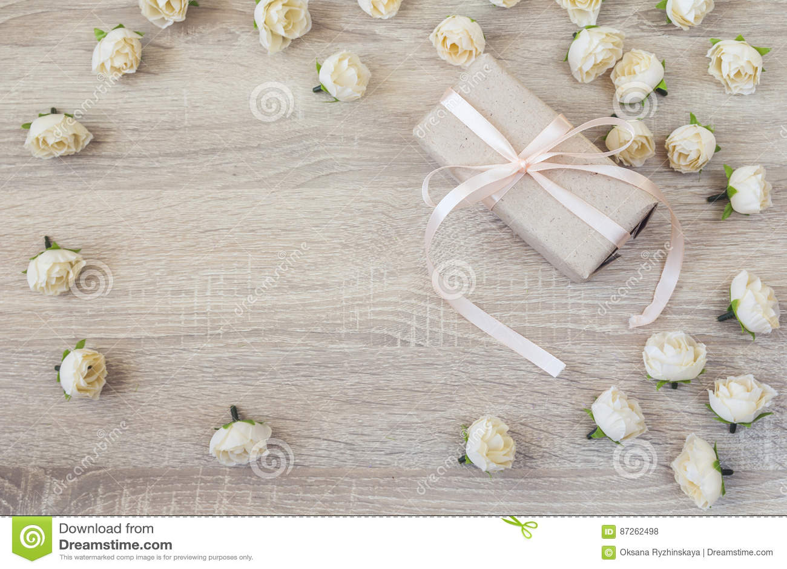 Caixa de presente com as rosas da fita e do pêssego no fundo de madeira com emp