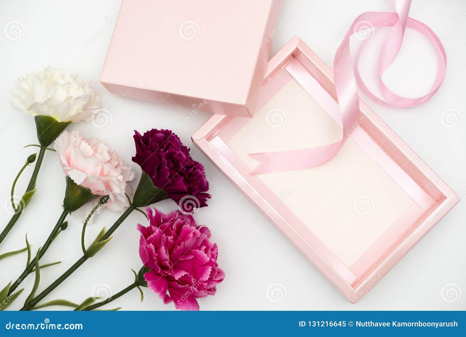 Caixa de presente cor-de-rosa com os cravos no branco