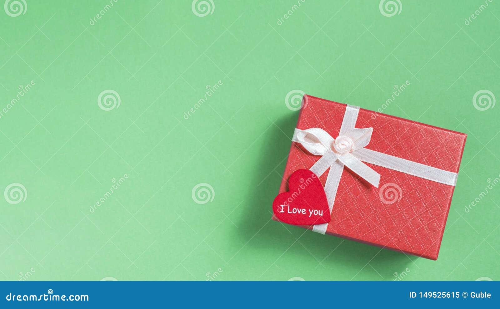 Caixa de presente cor-de-rosa com um coração vermelho em um fundo verde