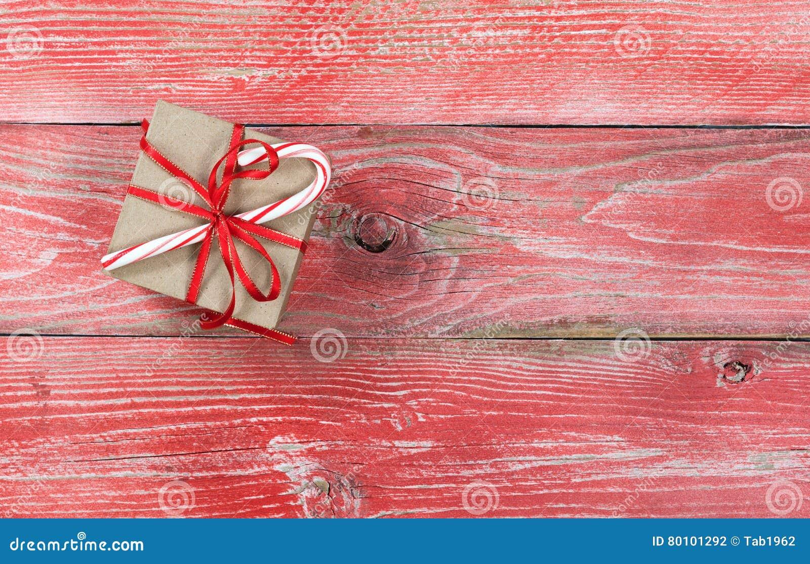Caixa de presente de época natalícia com o bastão de doces em placas de madeira vermelhas rústicas