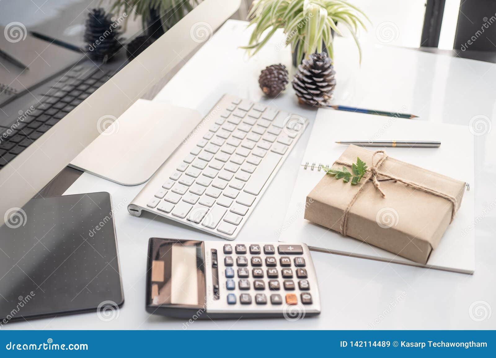 A caixa de presente envolveu o papel do ofício na mesa de escritório com computador do teclado, calculadora e fundo do caderno em