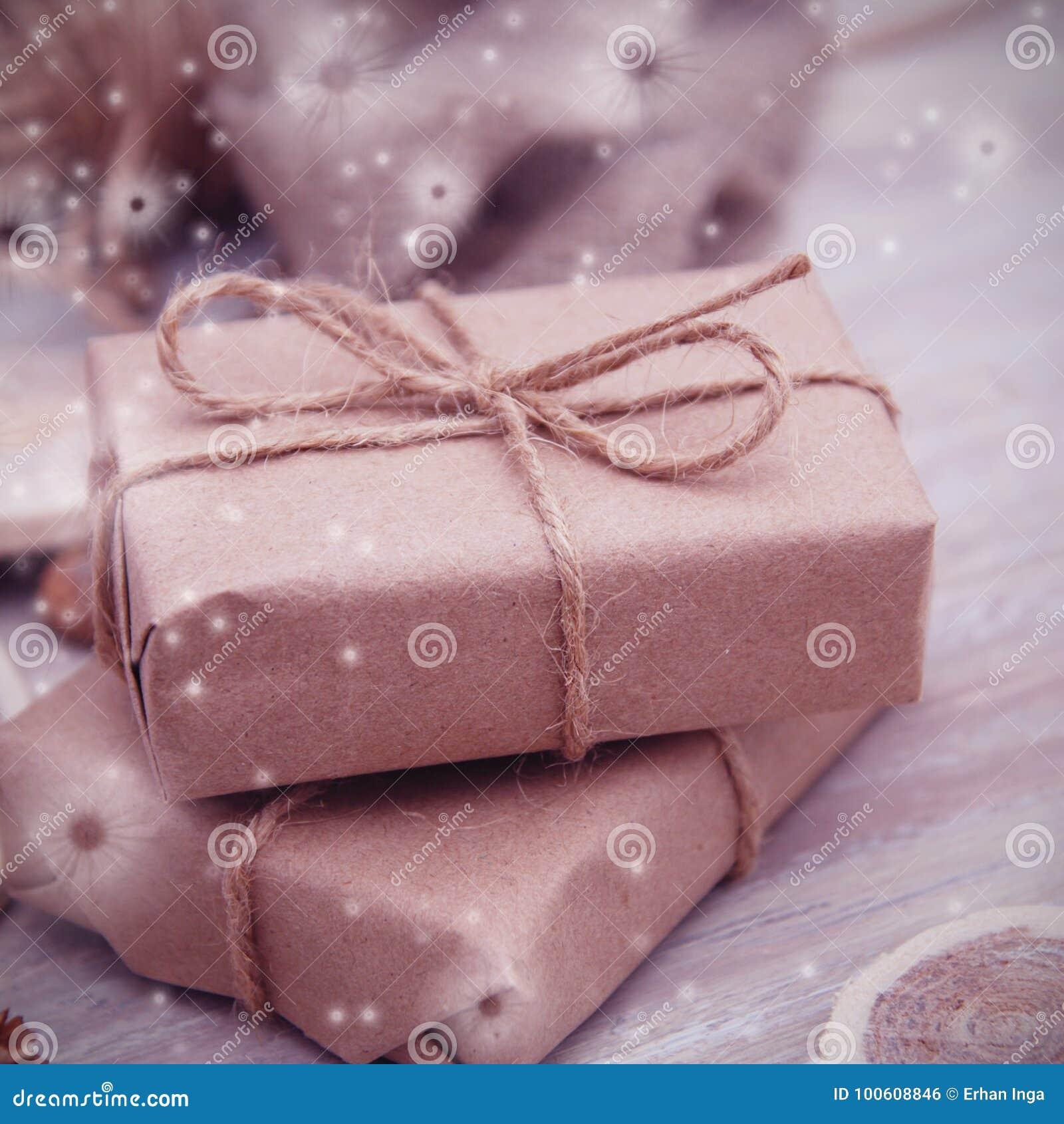 A caixa de presente envolvida no marrom reciclou o papel e amarrou a opinião superior da corda do saco no fundo branco, flocos de
