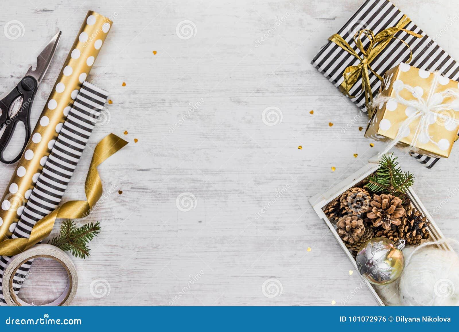Caixa de presente envolvida no papel listrado preto e branco com fita dourada, uma caixa completamente de cones do pinho e de bri