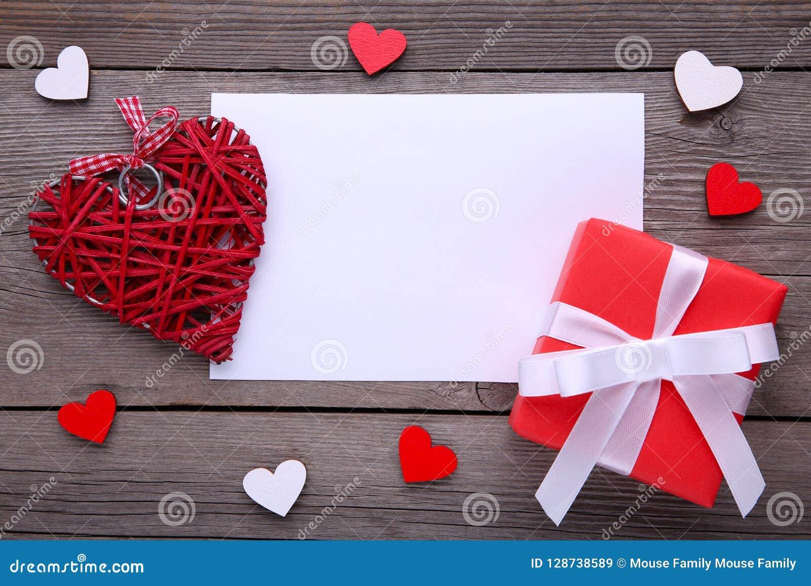 Caixa de presente vermelha com corações no fundo cinzento