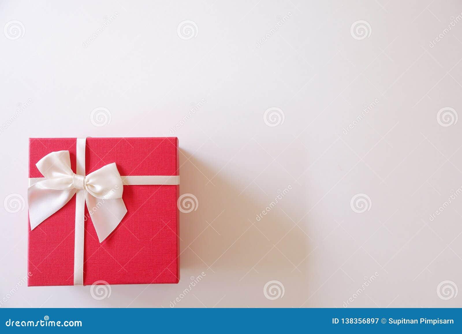 Caixa de presente vermelha do close-up com a fita branca no fundo branco
