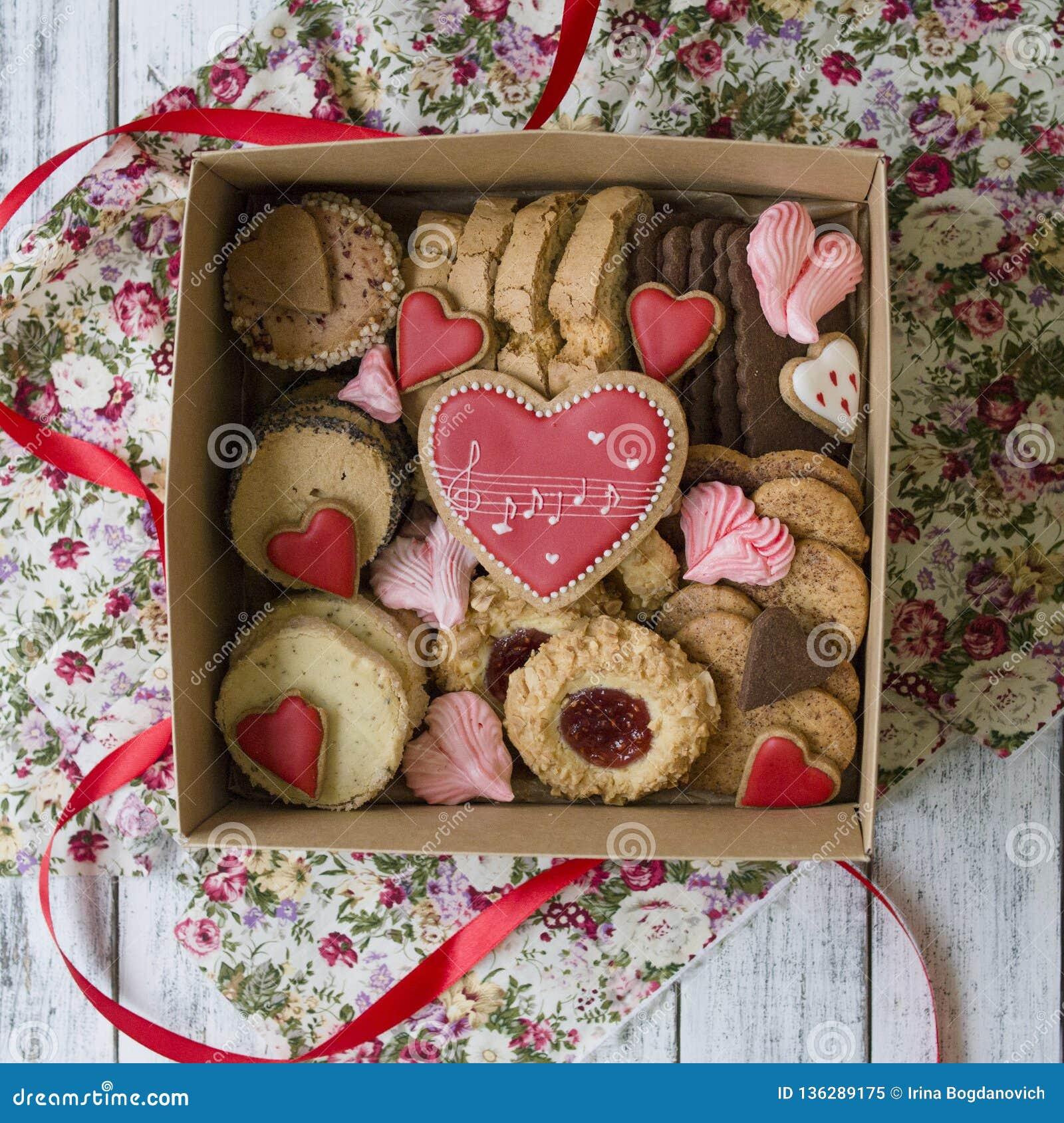 Caixa dos doces: cookies, marshmallow, merengue em uma caixa na tabela, cookies na forma de um coração um presente romântico para