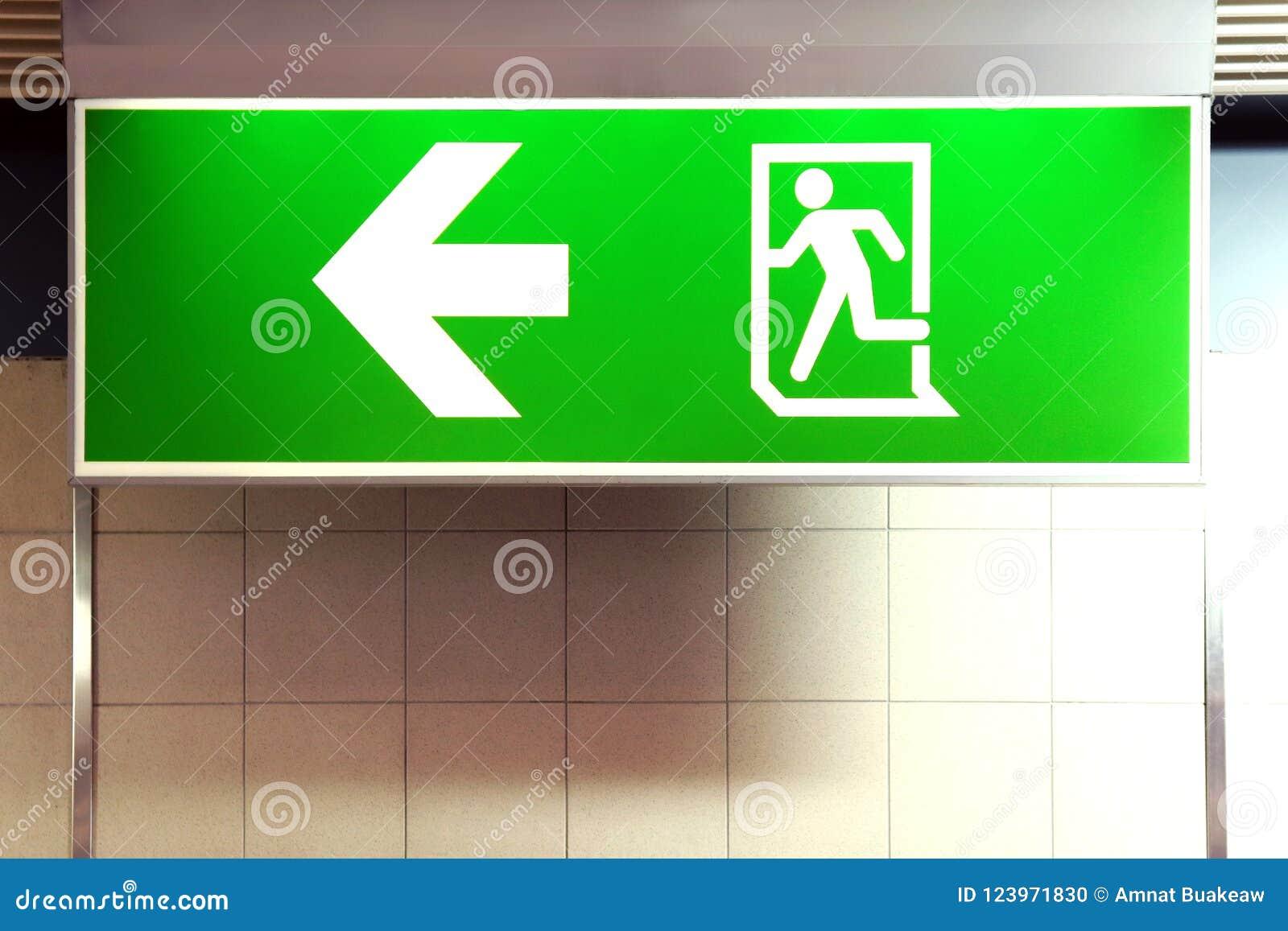 A caixa leve da saída de emergência velha na parede, sinal de aviso para o escape de fogo, alarme de incêndio assina, verde do si