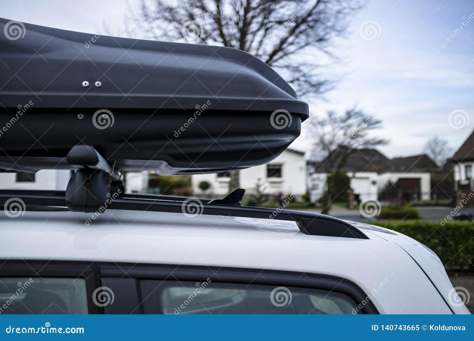 Caixa montada Closed do tronco ou da carga no telhado do carro, antes de uma viagem das férias em família, contra um céu azul, ár