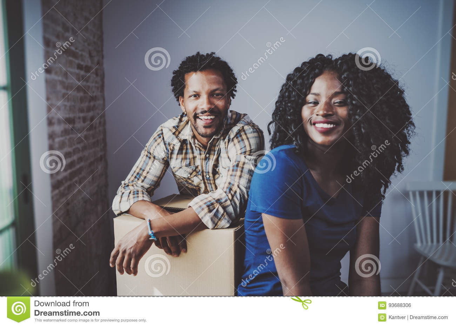 Caixas moventes dos pares novos felizes do africano negro no apartamento novo junto e fazendo uma vida bem sucedida Família alegr