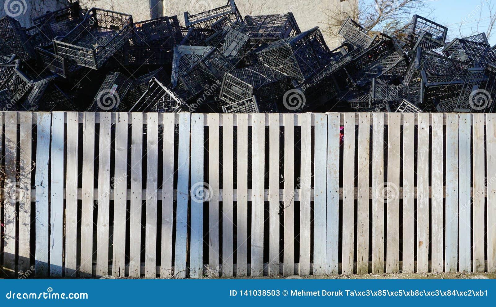 Caixas plásticas recicladas atrás da cerca branca
