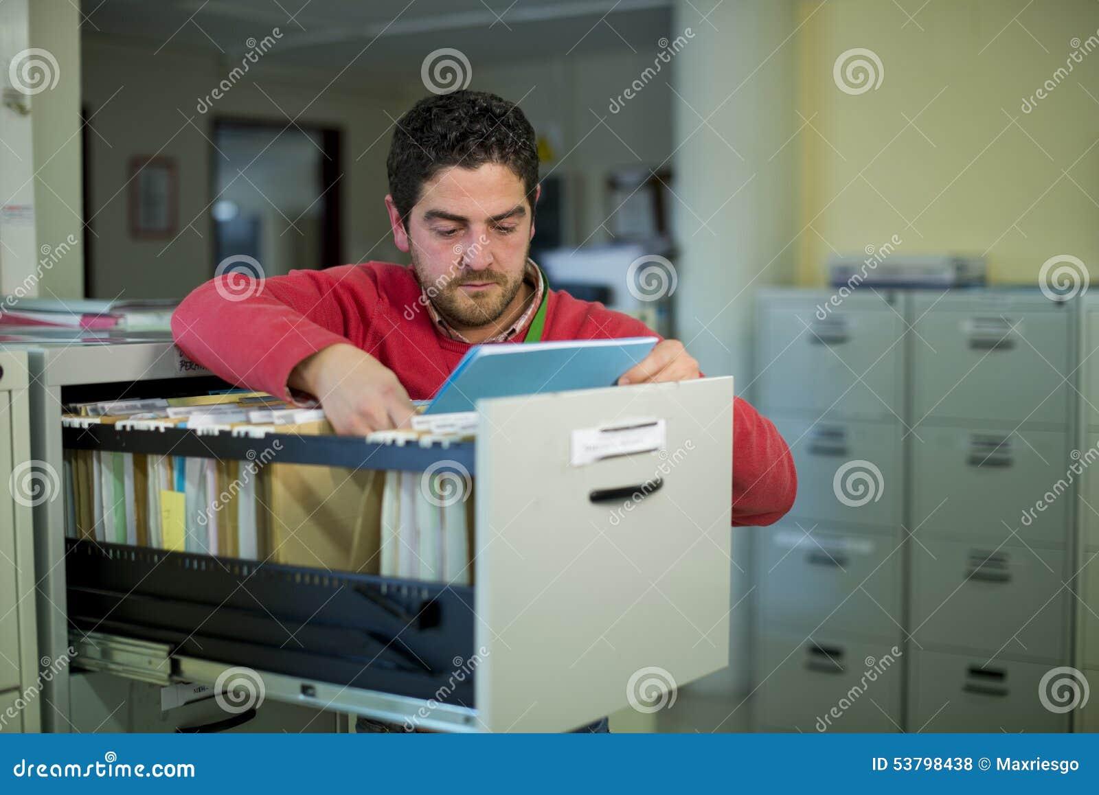 Caixeiro de escritório que olha alguns arquivos