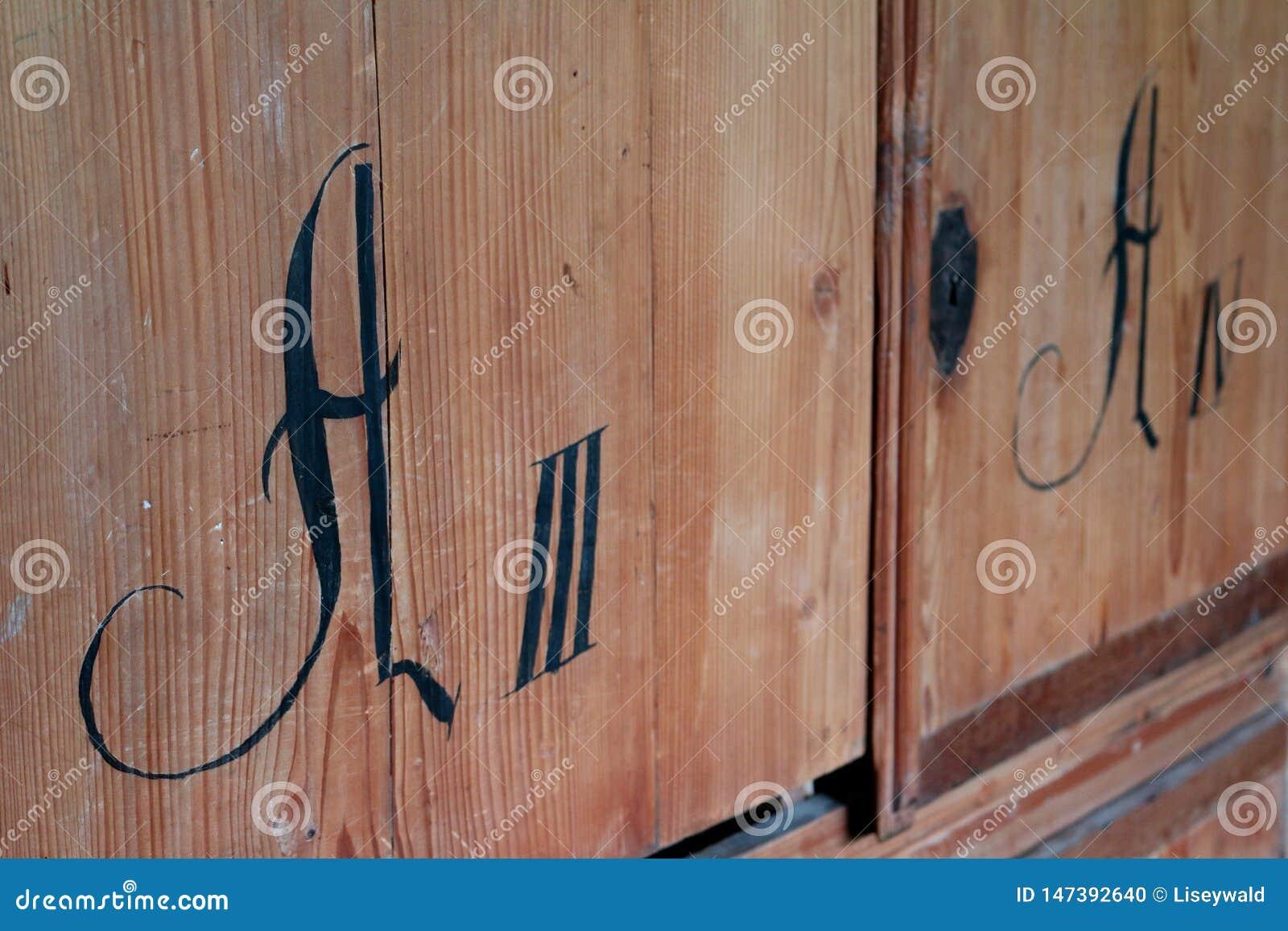 Cajón de madera de un armario antiguo con las letras latinas negras y los números romanos
